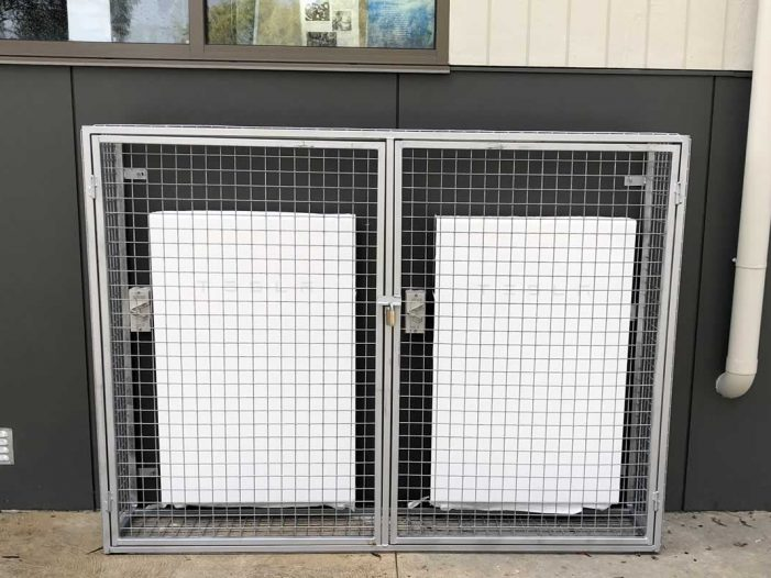 Tesla Powerwall 2 batteries installed in protective cage